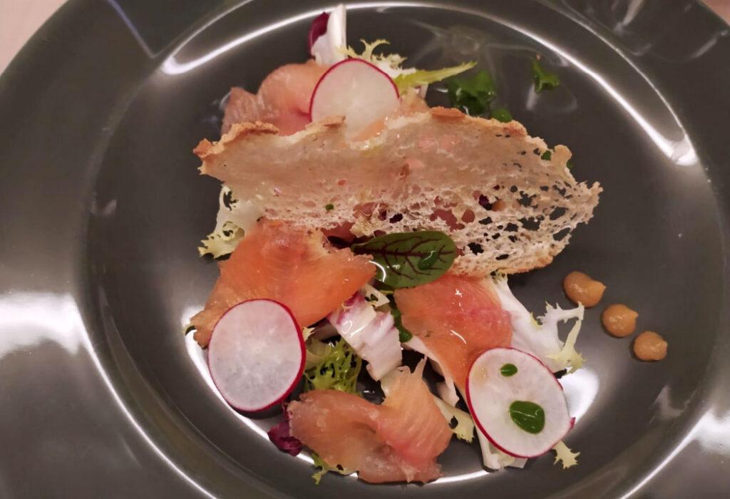trota salmonata marinata agli agrumi, su letto di misticanza con gel al melone,