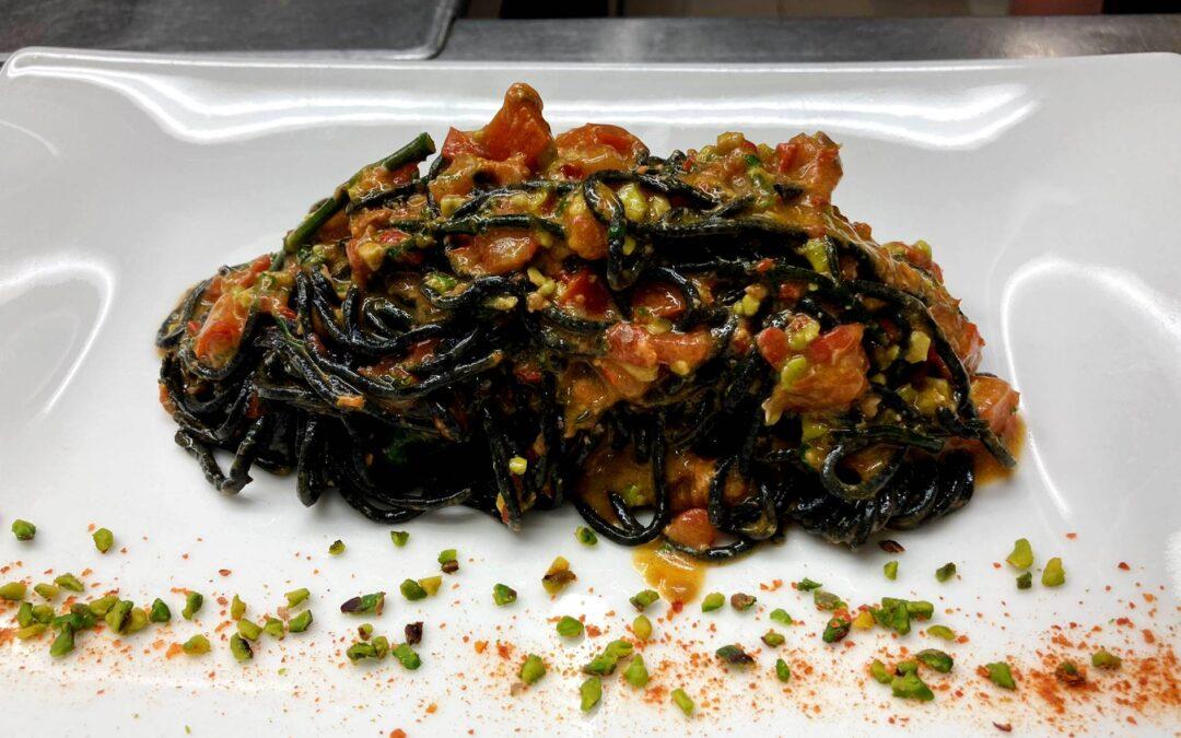 Chitarrina al nero al pesto di datterini e pistacchio di Bronte con riccio di mare e salicornia